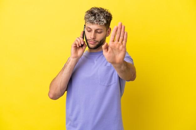 Jeune homme caucasien utilisant un téléphone portable isolé sur fond jaune faisant un geste d'arrêt et déçu