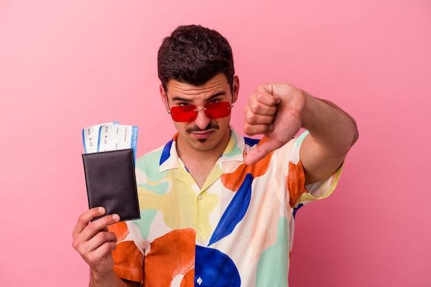 Jeune homme caucasien de voyageur tenant un passeport isolé sur fond rose montrant un geste d'aversion, les pouces vers le bas. notion de désaccord.