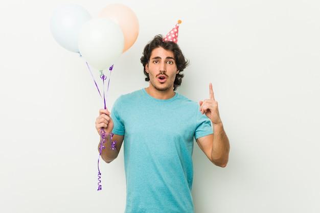 Jeune homme célébrant une fête tenant des ballons ayant une bonne idée