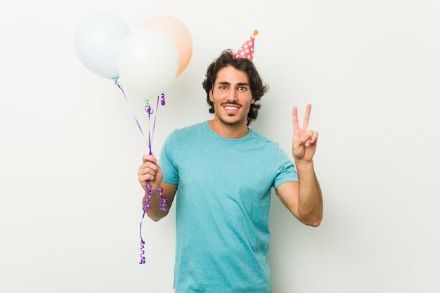 Jeune homme célébrant une fête tenant des ballons montrant le numéro deux avec les doigts.