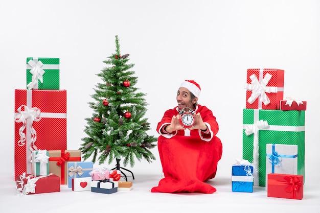 Jeune homme célèbre les vacances de noël assis dans le sol et montrant l'horloge près de cadeaux et arbre de noël décoré