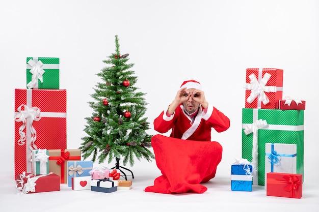 Jeune homme célébrer les vacances de noël assis dans le sol faisant des lunettes près de cadeaux et arbre de noël décoré