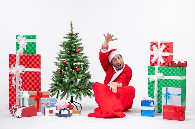 Jeune homme célébrer les vacances de noël assis dans le sol montrant quelque chose près de cadeaux et arbre de noël décoré