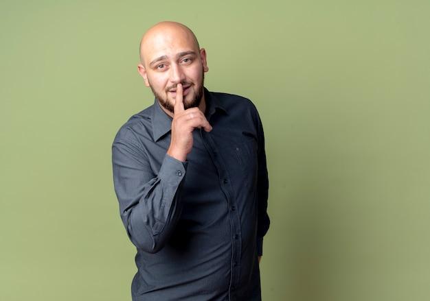 Jeune homme de centre d'appels chauve regardant la caméra et faisant des gestes silence isolé sur fond vert olive avec espace copie