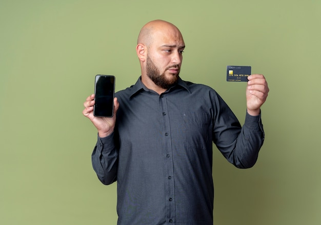 Jeune homme de centre d'appels chauve tenant le téléphone mobile et la carte de crédit et regardant la carte isolée sur fond vert olive avec espace de copie