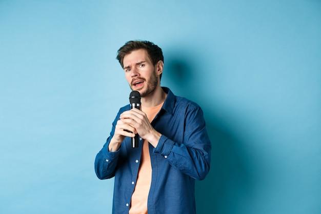 Jeune homme chantant la chanson dans le microphone, jouant au karaoké, debout sur fond bleu.