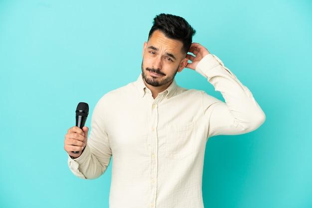 Jeune homme chanteur caucasien isolé sur fond bleu ayant des doutes