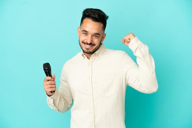 Jeune homme chanteur caucasien isolé sur fond bleu célébrant une victoire