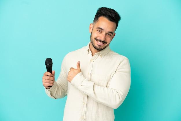 Jeune homme chanteur caucasien isolé sur fond bleu donnant un geste du pouce vers le haut