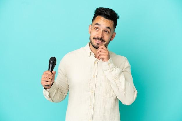 Jeune homme chanteur caucasien isolé sur fond bleu pensant à une idée tout en levant les yeux