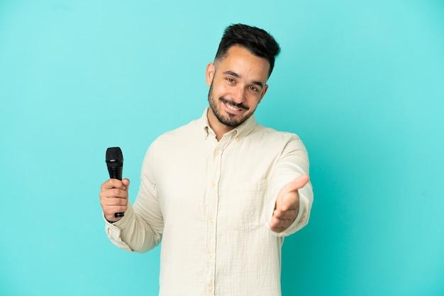 Jeune homme chanteur caucasien isolé sur fond bleu se serrant la main pour conclure une bonne affaire