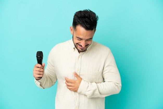 Jeune homme chanteur caucasien isolé sur fond bleu souriant beaucoup
