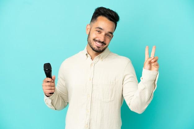 Jeune homme chanteur caucasien isolé sur fond bleu souriant et montrant le signe de la victoire