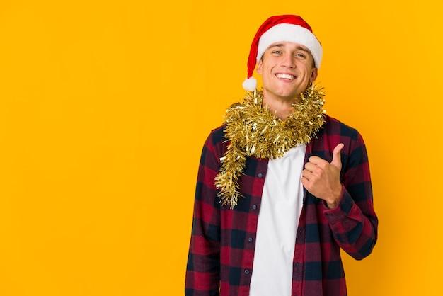 Jeune homme avec chapeau de noël tenant un cadeau isolé sur un mur jaune souriant et levant le pouce vers le haut