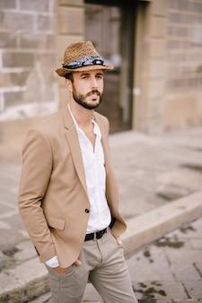 Un jeune homme avec un chapeau de paille, une chemise blanche déboutonnée et une veste de sable, une petite barbe se promène dans la ville de florence
