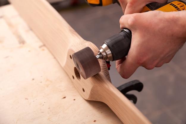 Jeune homme charpentier égale la planche de bois polie