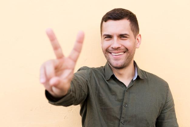 Jeune homme chaume montrant le geste de la paix sur fond beige