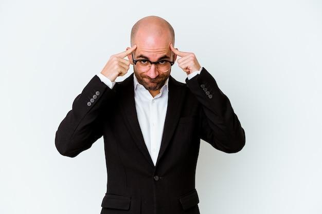 Jeune homme chauve d'affaires isolé sur mur bleu axé sur une tâche, gardant l'index pointant la tête
