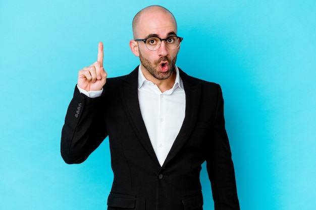 Jeune homme chauve d'affaires isolé sur mur bleu pointant vers le haut avec la bouche ouverte