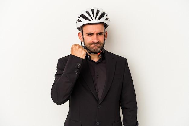 Jeune homme chauve d'affaires portant un casque de vélo isolé sur fond blanc montrant le poing à la caméra, expression faciale agressive.