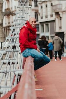 Jeune homme chauve assis au bord d'un pont de la ville de lyon