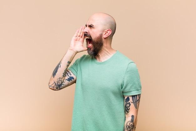 Jeune homme chauve et barbu criant fort et avec colère pour copier l'espace sur le côté, avec la main à côté de la bouche