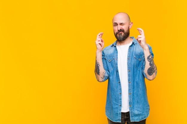 Jeune homme chauve et barbu croisant les doigts avec anxiété et espérant avoir de la chance avec un regard inquiet