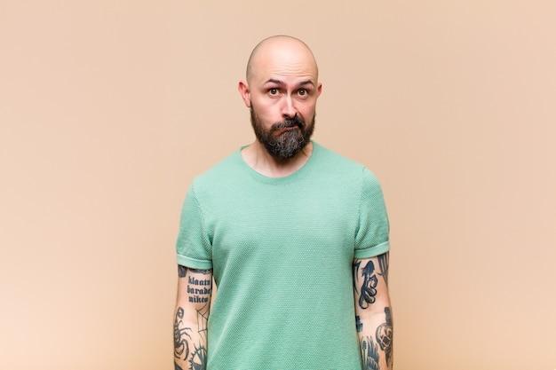 Jeune homme chauve et barbu avec une expression maladroite, folle, surprise, les joues gonflées, se sentant bourré, gras et plein de nourriture
