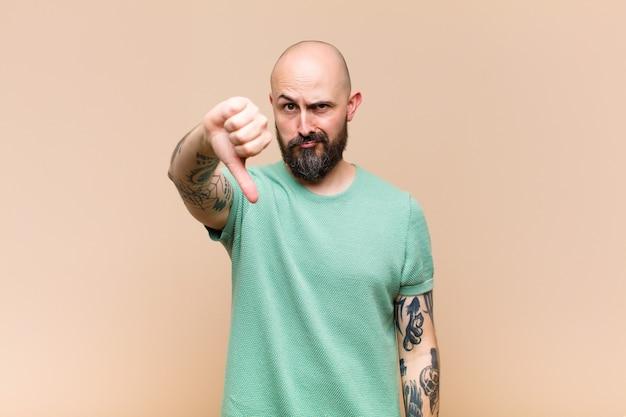 Jeune homme chauve et barbu se sentant croisé, en colère, ennuyé, déçu ou mécontent, montrant les pouces vers le bas avec un regard sérieux