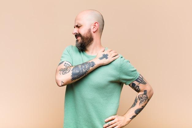 Jeune homme chauve et barbu se sentant fatigué, stressé, anxieux, frustré et déprimé, souffrant de douleurs au dos ou au cou