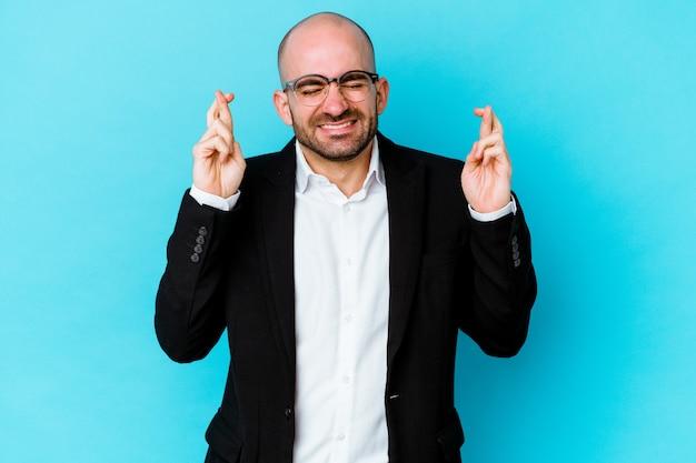 Jeune homme chauve caucasien d'affaires isolé sur fond bleu croisant les doigts pour avoir de la chance