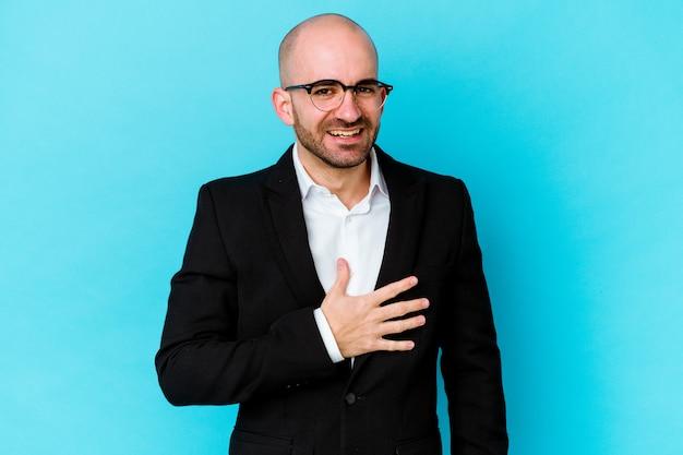 Jeune homme chauve caucasien d'affaires isolé sur fond bleu éclate de rire en gardant la main sur la poitrine.