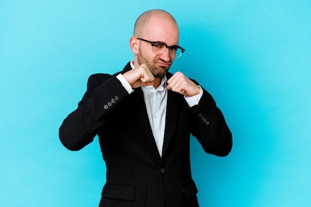 Jeune homme chauve caucasien d'affaires isolé sur fond bleu jetant un coup de poing, colère, combat à cause d'une dispute, boxe.