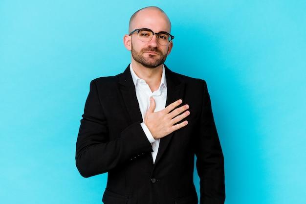 Jeune homme chauve caucasien d'affaires isolé sur fond bleu en prêtant serment, mettant la main sur la poitrine.