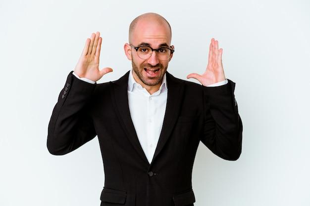 Jeune homme chauve caucasien d'affaires isolé sur fond bleu recevant une agréable surprise, excité et levant les mains.