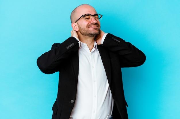 Jeune homme chauve caucasien d'affaires isolé sur fond bleu se sentant confiant, avec les mains derrière la tête.