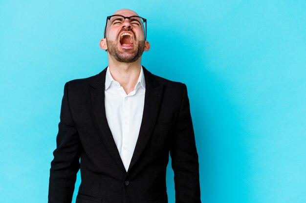 Jeune homme chauve caucasien d'affaires isolé sur mur bleu criant très en colère
