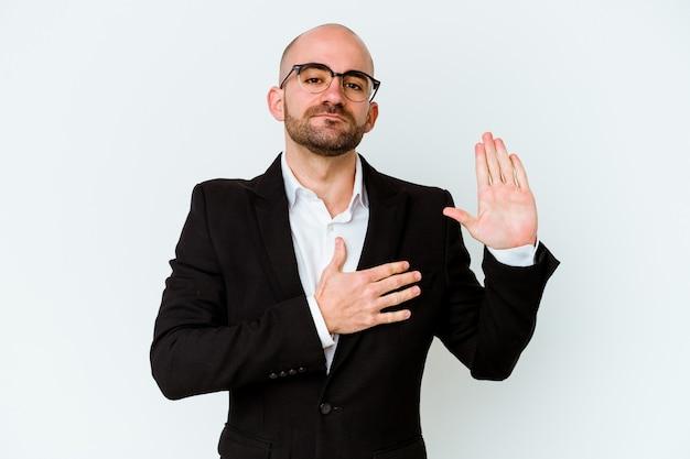 Jeune homme chauve caucasien d'affaires isolé sur un mur bleu en prêtant serment, mettant la main sur la poitrine.