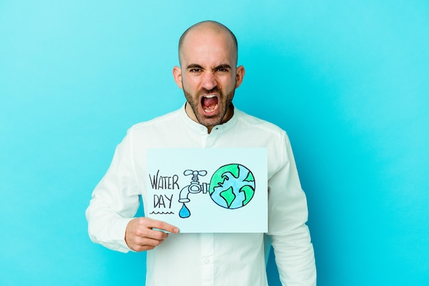 Jeune homme chauve caucasien célébrant la journée mondiale de l'eau isolée sur fond bleu criant très en colère et agressif.