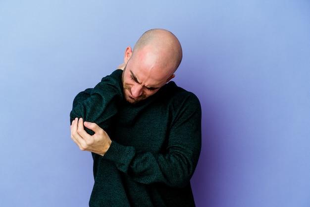 Jeune homme chauve caucasien sur le coude de massage violet, souffrant après un mauvais mouvement.