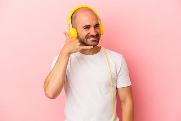 Jeune homme chauve caucasien écoutant de la musique isolée sur fond rose montrant un geste d'appel de téléphone portable avec les doigts.