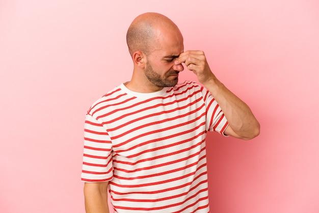 Jeune homme chauve caucasien isolé sur fond rose ayant un mal de tête, touchant le devant du visage.
