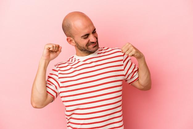 Jeune homme chauve caucasien isolé sur fond rose célébrant une journée spéciale, saute et lève les bras avec énergie.