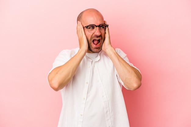 Jeune homme chauve caucasien isolé sur fond rose couvrant les oreilles avec les mains essayant de ne pas entendre un son trop fort.