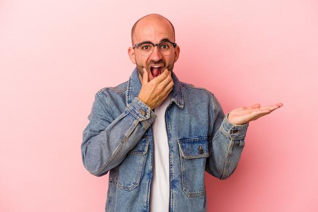Jeune homme chauve caucasien isolé sur fond rose détient un espace de copie sur une paume, gardez la main sur la joue. émerveillé et ravi.