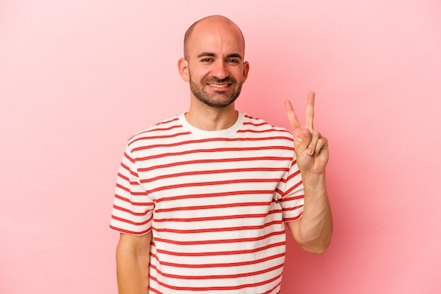 Jeune homme chauve caucasien isolé sur fond rose joyeux et insouciant montrant un symbole de paix avec les doigts.