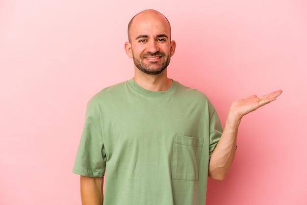 Jeune homme chauve caucasien isolé sur fond rose montrant un espace de copie sur une paume et tenant une autre main sur la taille.