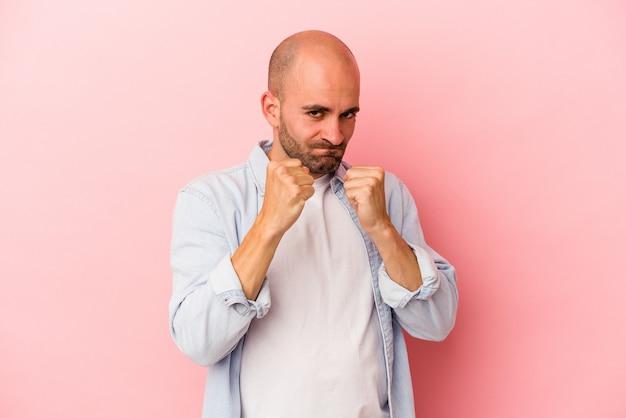 Jeune homme chauve caucasien isolé sur fond rose montrant le poing à la caméra, expression faciale agressive.