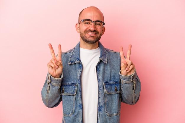 Jeune homme chauve caucasien isolé sur fond rose montrant le signe de la victoire et souriant largement.
