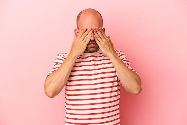 Jeune homme chauve caucasien isolé sur fond rose peur couvrant les yeux avec les mains.